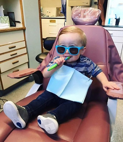A small child learning how to brush his teeth at Sylvan Heights Dental in Portland, OR