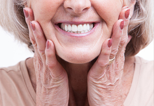 Senior woman smiling after receiving dentures at Sylvan Heights Dental